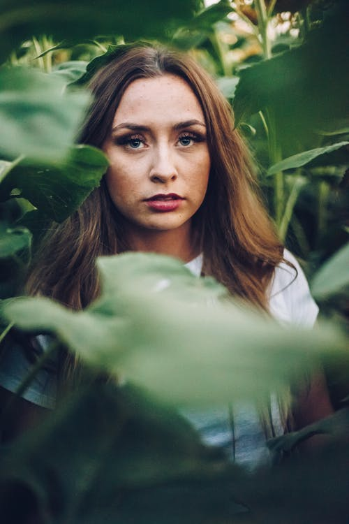 Young trendy female with makeup and focused gaze standing among bright shrubs and looking away