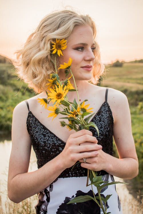 Dreamy woman in elegant apparel with blooming flowers in countryside