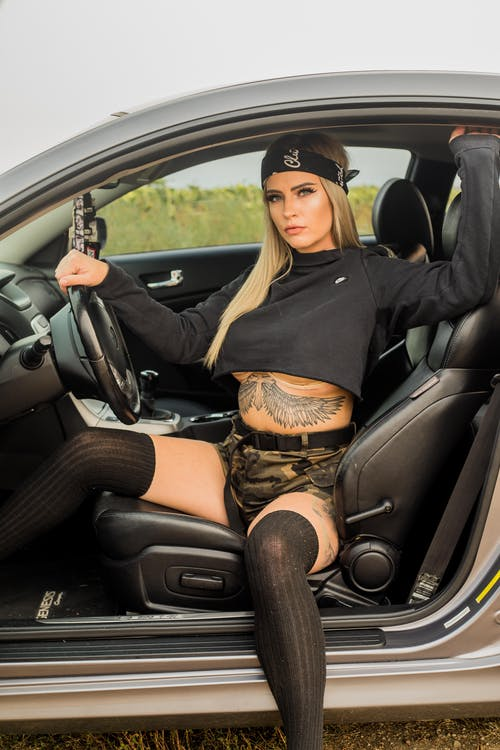 Young sensual female with tattoos in trendy wear sitting on leather seat in auto and looking at camera