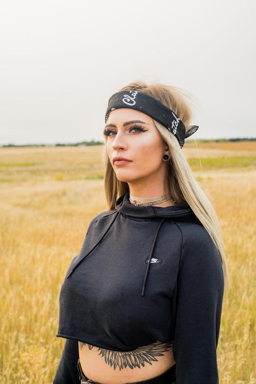 Young focused blond female in stylish clothes with tattoo on belly and makeup looking at camera under white sky