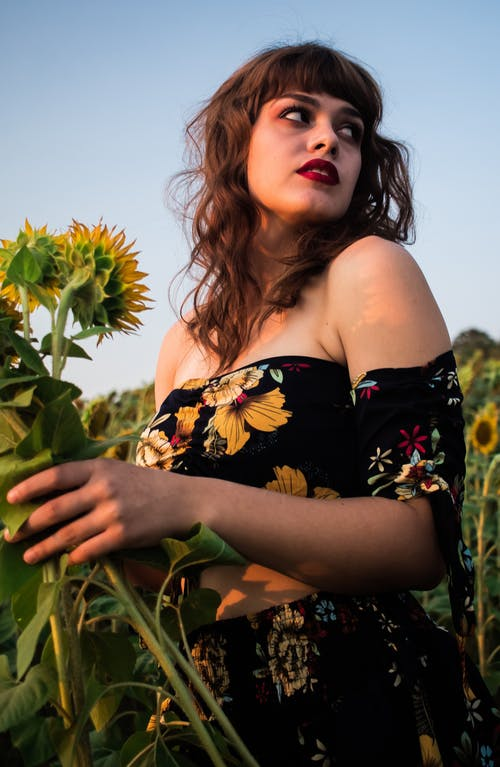 Stylish woman with makeup and sunflowers in field