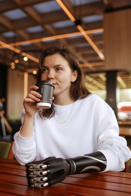 Woman With a Prosthetic Hand Holding a Paper Coffee Cup