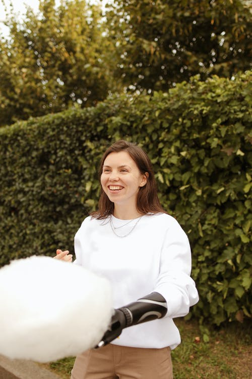 Woman With a Prosthetic Hand Holding Cotton Candy