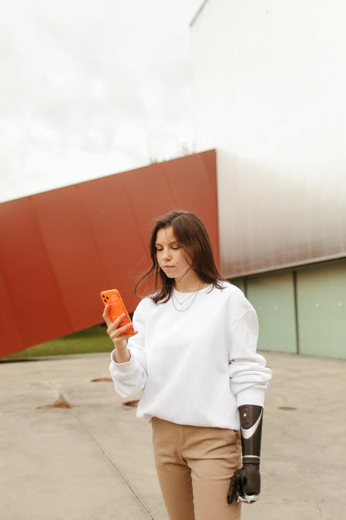 Woman With a Prosthetic Hand Using her Smartphone