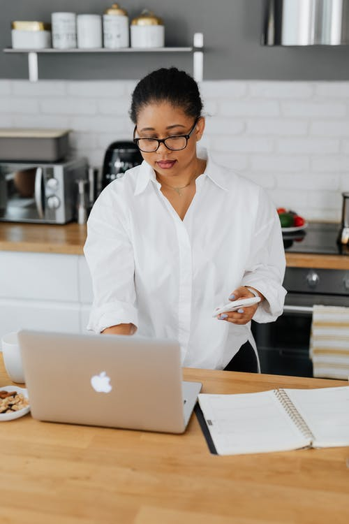 Woman in White Button-Up Shirt Using a Laptop and a Cellphone