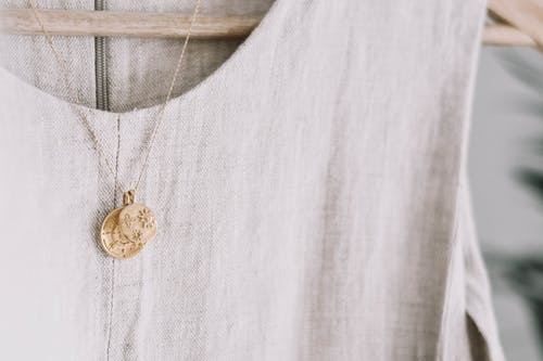 Gold Round Pendant Necklace on White Textile