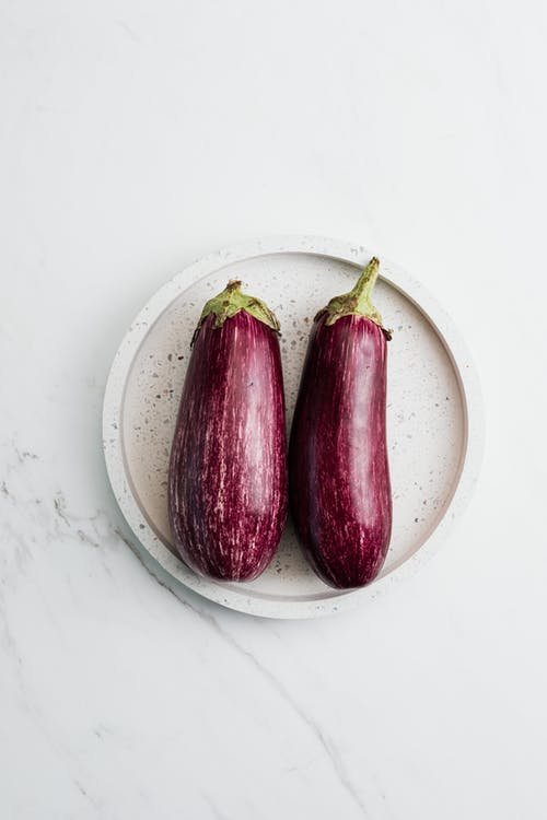 Two Eggplants on a White Plate