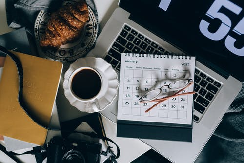 Calendar on a Laptop Beside a Cup of Black Coffee