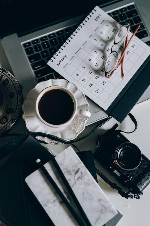 Cup of Black Coffee Beside a Calendar