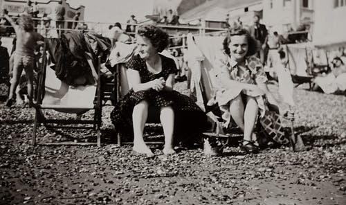 Grayscale Photo of Women Sitting on Chairs Outdoors