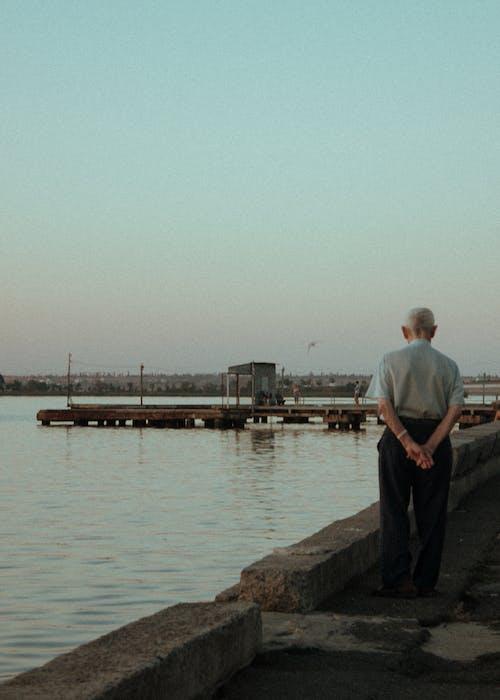 Elderly Man in White Shirt Standing on Concrete Dock