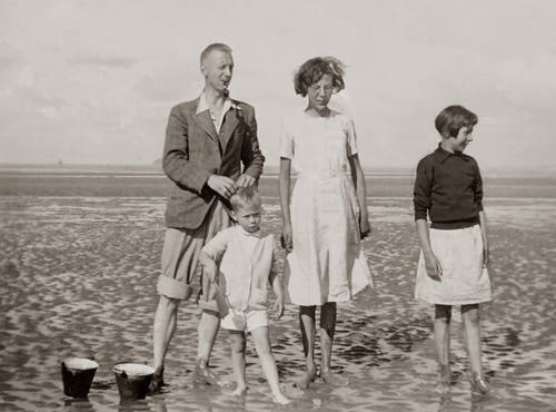 Grayscale Photo of a Family Standing on the Beach