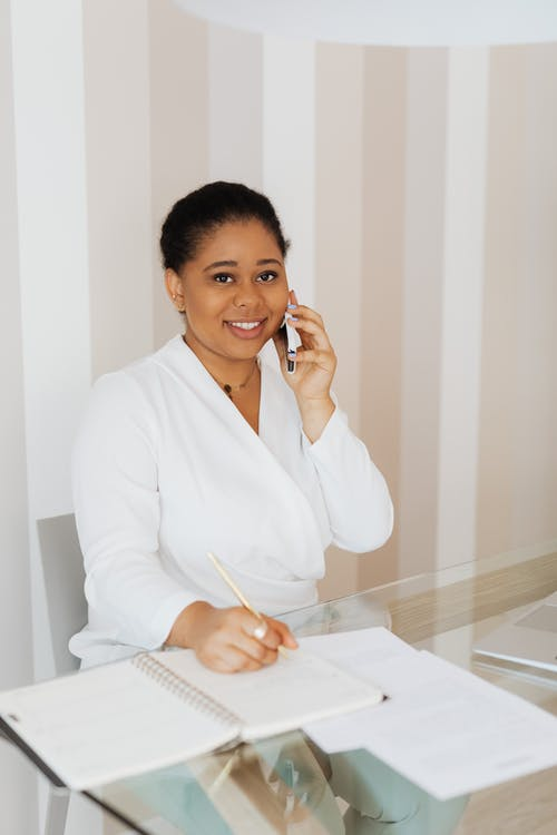Woman in White Top Smiling while Holding Cellphone