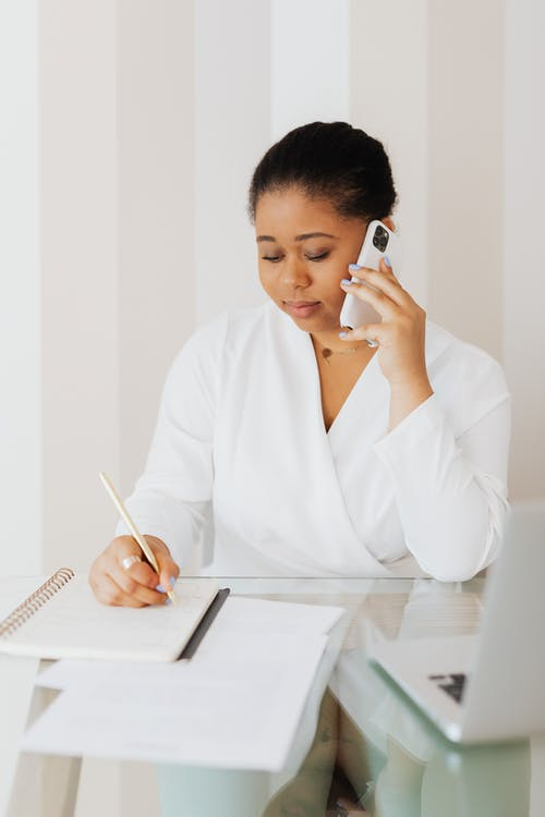 Woman in White Top Writing on Notebook while Talking on Cellphone