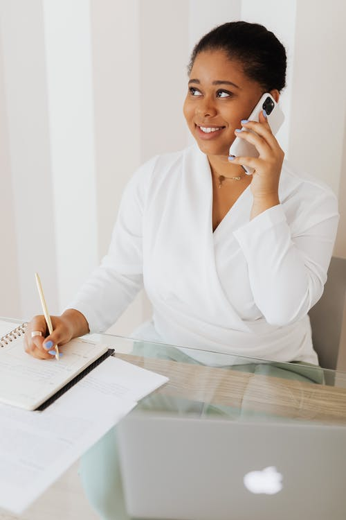 Woman in White Top Talking on Cellphone while Writing on Notebook