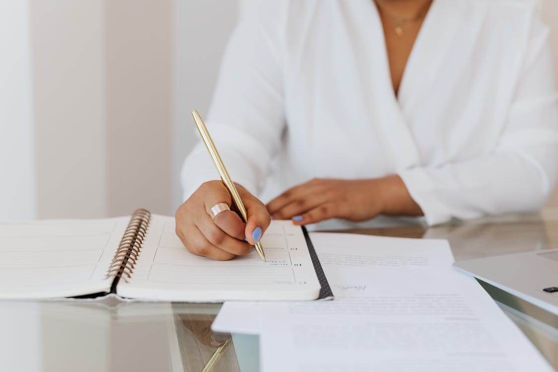 Person in White Top Writing on Notebook