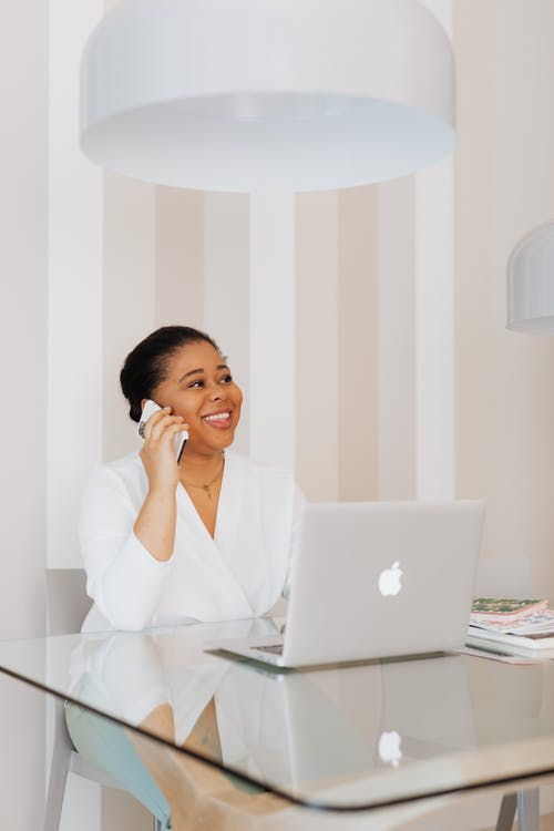 Smiling Woman in White Top Having a Phone Call