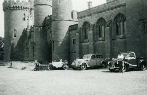 Grayscale Photo of Cars Parked Near a Building