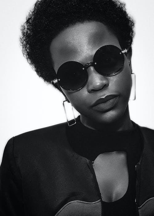 Black and white crop confident African American female in stylish sunglasses and accessories in studio with white background