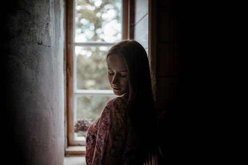 Woman in Floral Dress Standing Beside Window