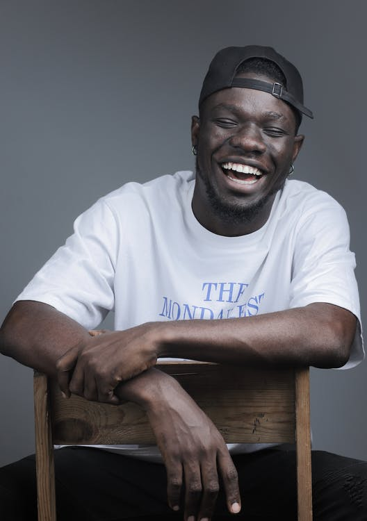 Cheerful black man sitting on chair