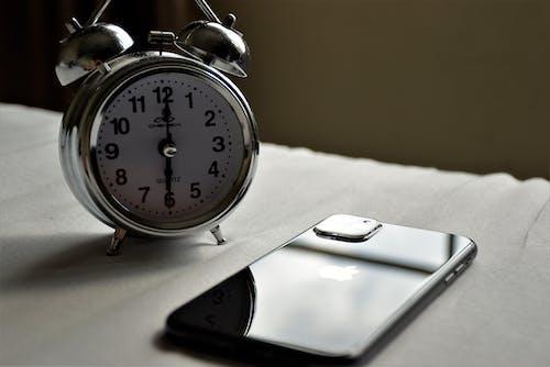 Silver Alarm Clock beside an Iphone