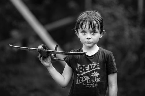 Grayscale Photo of Boy Holding an Airplane Toy