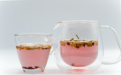 Glass transparent teapot with fresh brewed herbal tea placed near cup in studio