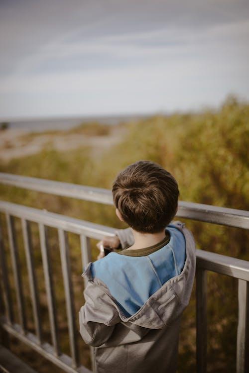 Unrecognizable boy standing near park railing