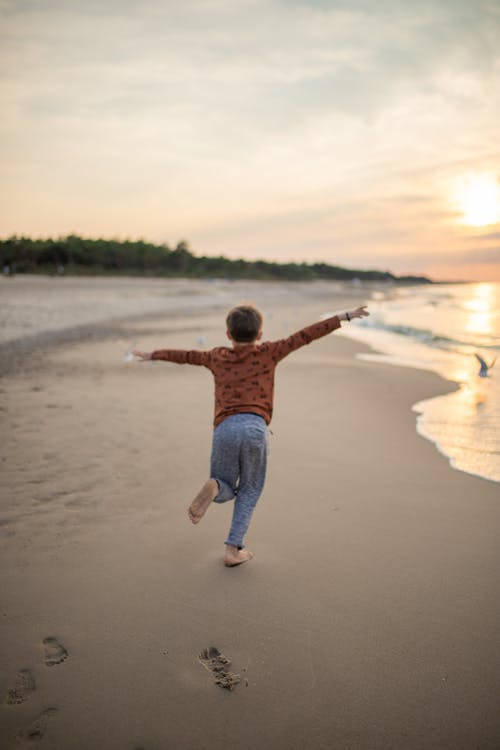 Faceless carefree boy walking on sandy beach with arms outstretched