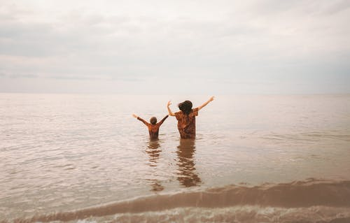 Unrecognizable woman and son standing in seawater with arms outstretched