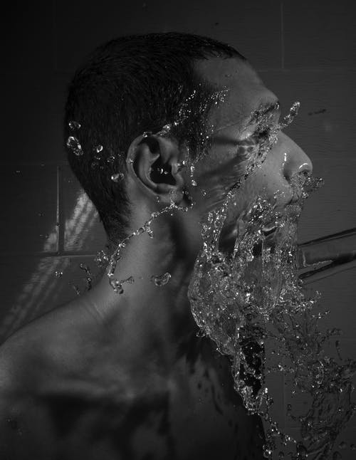 Grayscale Photo of Man with Water on His Face