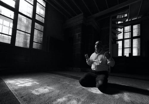 Anonymous ethnic man praying on knees in temple