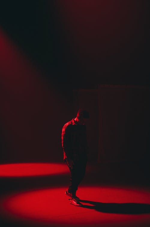 Full body silhouette of anonymous tired male walking in dark room with red illumination
