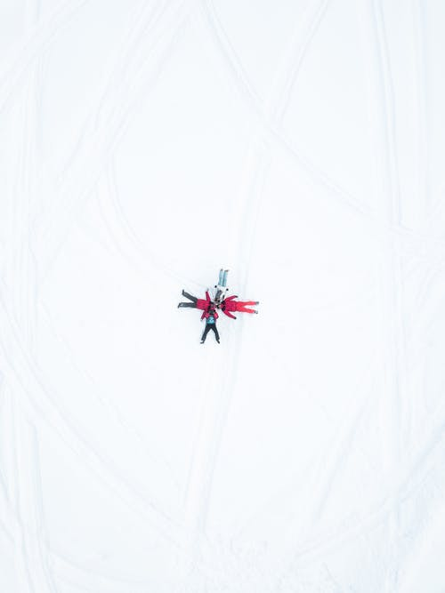 Top View of People Lying Down on Snow Covered Ground