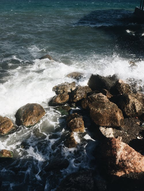 Stormy sea waves washing rocky shore in sunlight