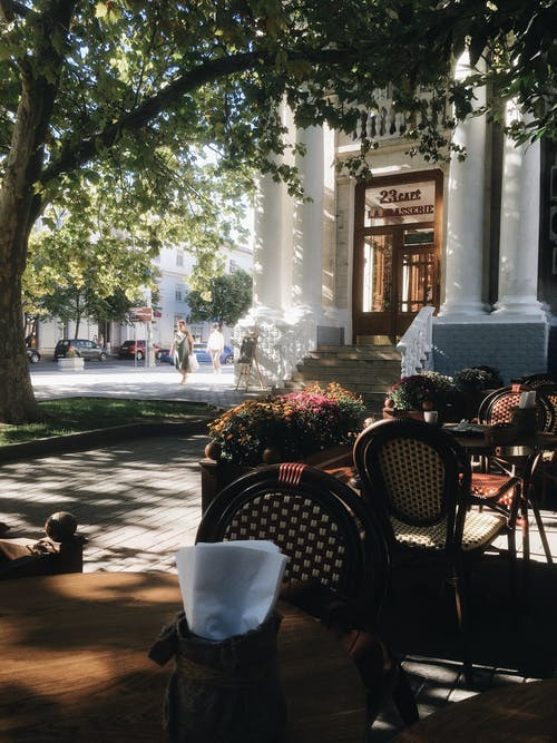 Stylish street cafe near building with columns in sunlight