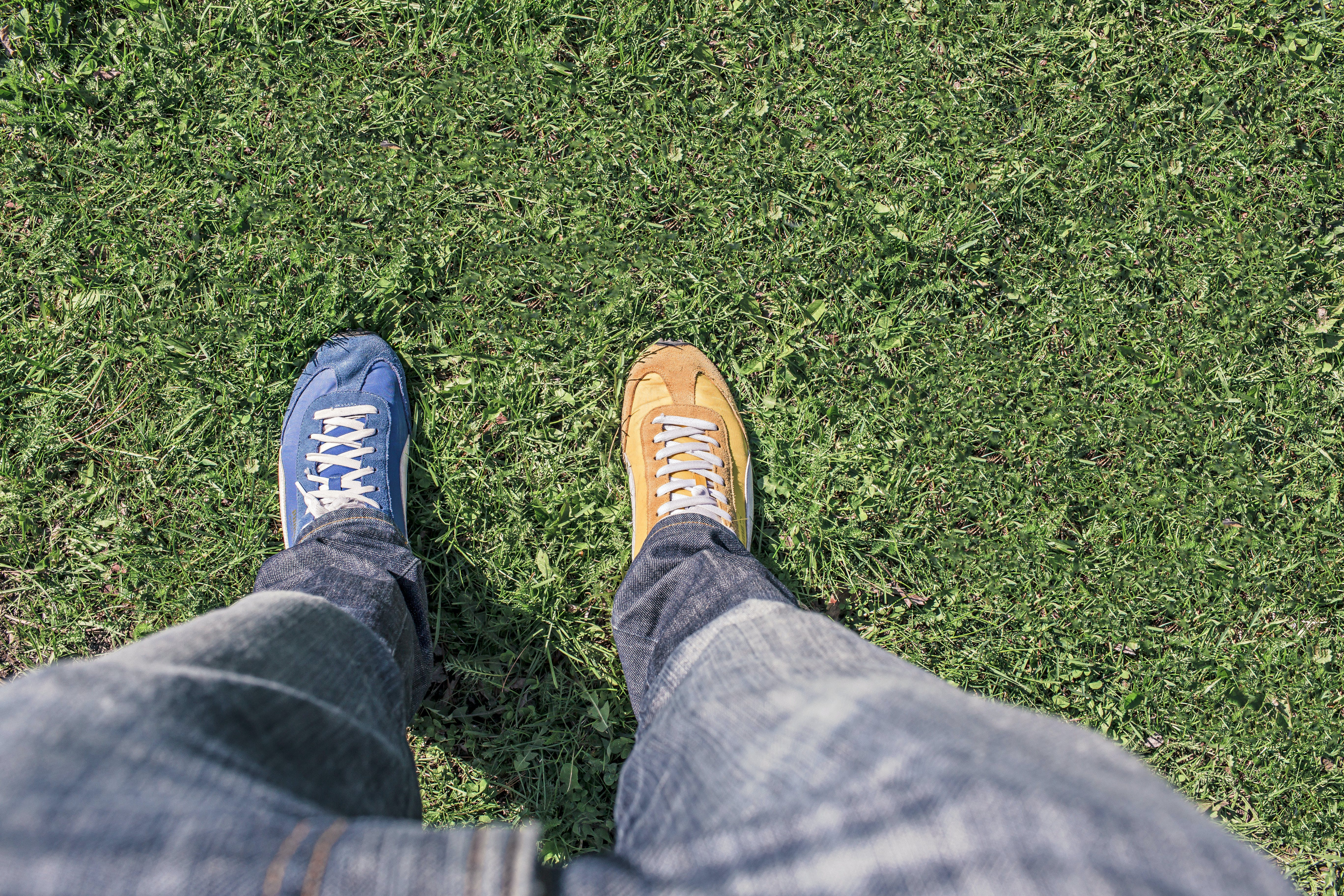Person Wearing Unpaired Running Shoes Standing on Green Grass