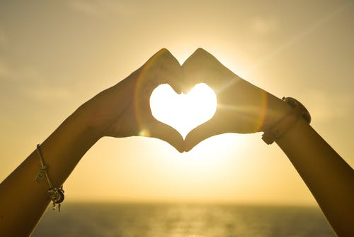 Two People Forming Heart Sign to Sun