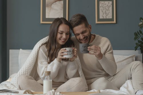 Couple Smiling while Having Their Breakfast in Bed
