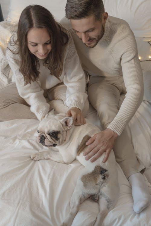 A Couple Cuddling Their Cute Dog