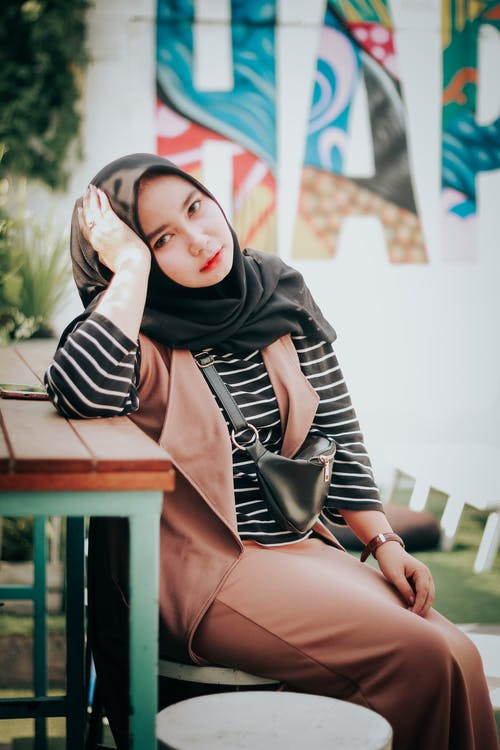 Woman in Black Hijab Sitting on Picnic Table
