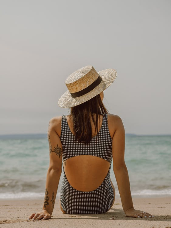 Woman with tattoos in swimsuit and hat resting on sandy beach
