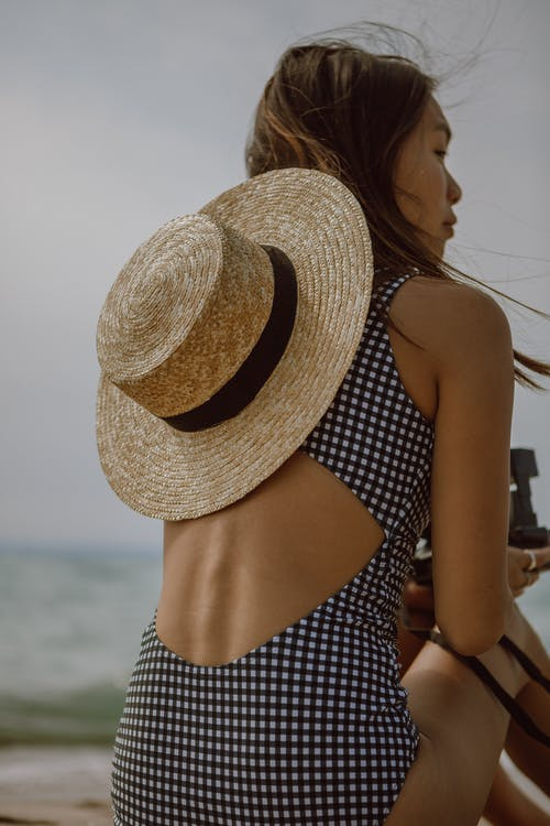 Back view of calm young ethnic female in swimsuit and straw hat relaxing on sandy beach with photo camera in hands and looking away
