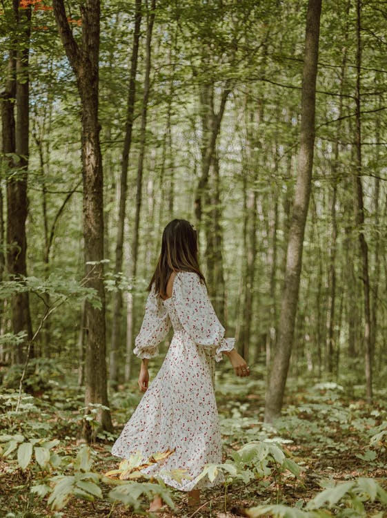 Side view of unrecognizable young slim female in romantic maxi dress walking in green forest amidst lush green trees on sunny day
