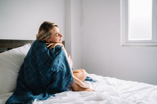 Woman Covered with a Blue Blanket Sitting on Bed