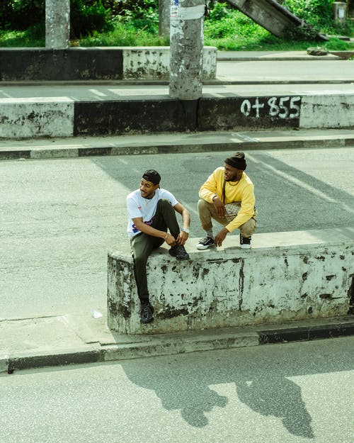 From above full length content African American males in street style resting on concrete highway barrier and chatting on sunny summer weather