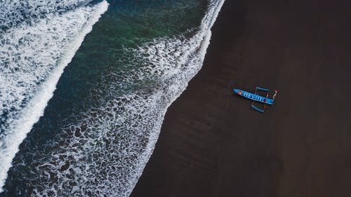 Aerial View of Blue and White Boat on Sea