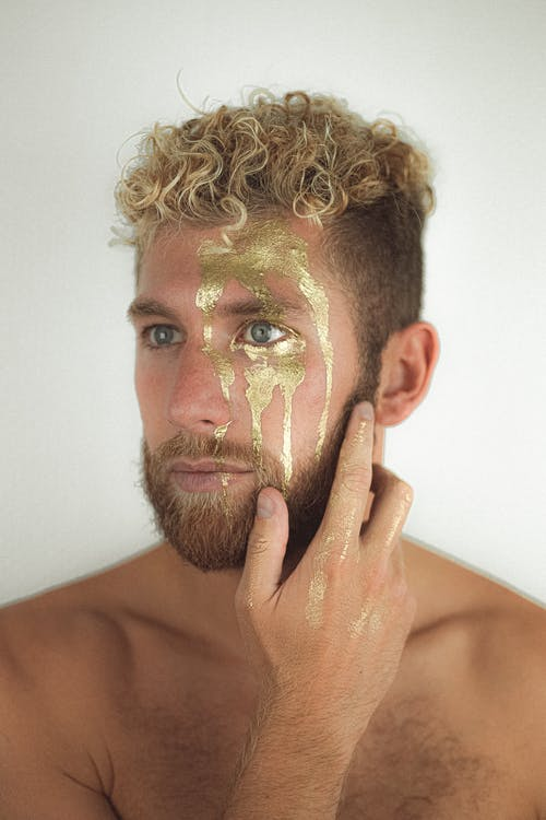 Handsome shirtless male with golden paint on face