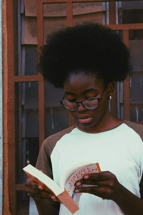 Black student in eyeglasses reading book near wall